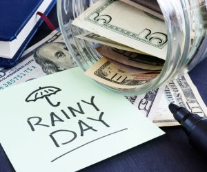 Rainy day fund savings. Jar with dollar bills.