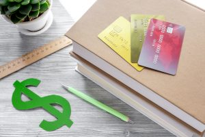 dollar sign and credit cards for fee-paying education on gray student desk background
