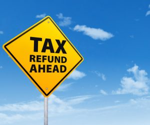 Tax refund concept with a road sign under blue sky