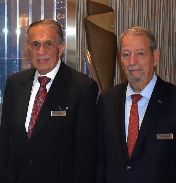 Nicholas Lorusso and Barry Minkin standing next to each other in black suits, with red ties.