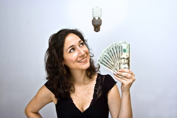 Woman waving money and looking up. Having an environmentally friendly idea with an energy saving flourescent light bulb floating above her head.